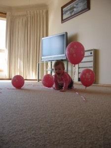 Baby girl among balloons
