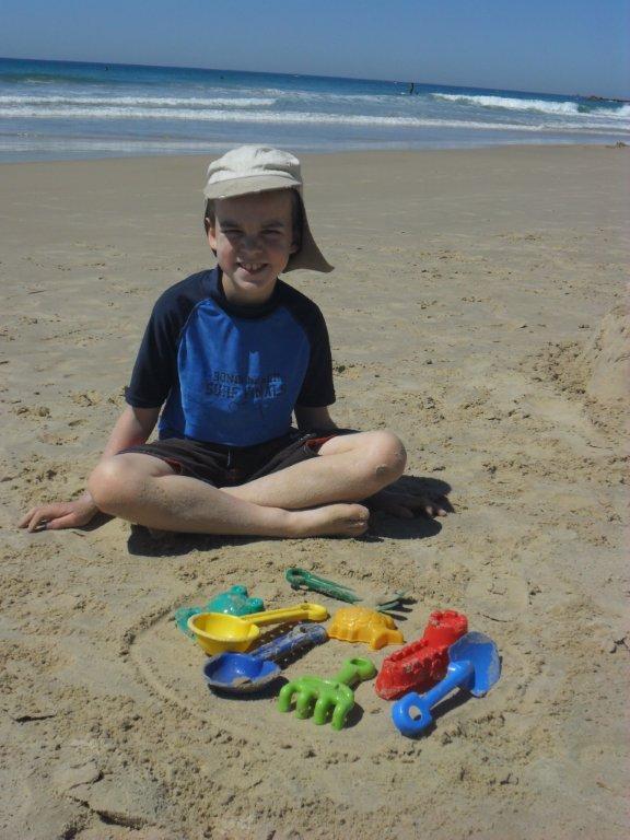 boy on the beach with beach toys