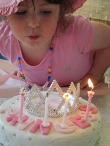 blowing out four year old's birthday candles on princess tiara cake