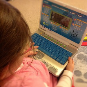 girl on toy computer