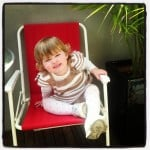 child in red chair